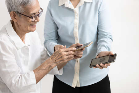 Asian woman teaching the old people how to use mobile phone,Happy smiling senior grandma learning to use smartphone,scanning the QR code,use the application how add for friend,technology for elderly