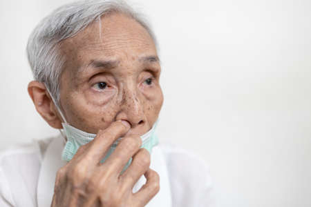 Elderly people is picking nose with finger inside,Do not touch nose with dirty hand,avoid touching,prevention form ,risk of infection,Don't touch face,health care,hygiene concept
