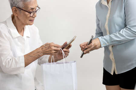 Senior woman buyer with shopping bags in hands buying goods and female seller in a store,old elderly using mobile phone scanning QR code payment digital wallet,contactless cashless society concept