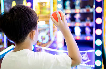 Kid boy playing a game of darts,holding a small plastic ball in his hands,aiming throwing at a target or a toy doll to knock it down,little child hurl the ball at the toys placed on the shelf to fall Stock Photo