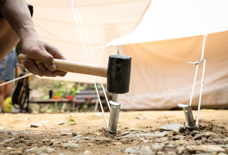Hand of man holding a rubber mallet,hammering aluminium steel tent stakes pegs nail,fastening tent for camping,hit or beat anchor of the tent into the ground,hammer with rubber head, wooden handle