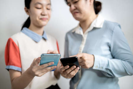Asian adult woman smirk smile with disdain on her face shows scornful abuse,dissatisfied teenage lady girl with disrespect expressing contempt,envy others,disgust as he reads a message on mobile phone Foto de archivo