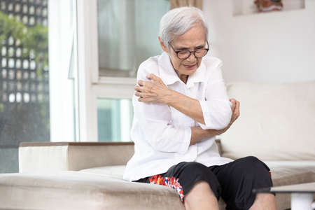 Itchy senior woman scratching arms with her hands,rash on body,pruritus,severe itching of the skin from food allergies,symptoms of hives,urticaria disease,patient allergic reaction,atopic dermatitis
