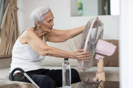 Overheated asian senior woman sweating,high temperature in sunny day while stay at home,cooling herself in front of an electric fan,old elderly suffering from heat,hot summer weather,lifestyle concept Stock Photo