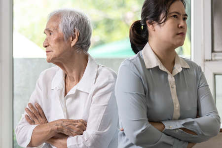 Displeased asian daughter sitting back to back after quarrel,argue feel offended at home,angry upset elderly mother with crossed arms,relationship difficulties,conflict,family crisis,lifestyle problem Stock Photo