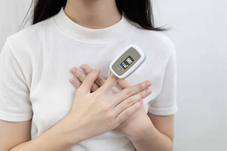 Hand of lady girl with fingertip pulse oximeter on finger for examination of the lung disease,checking for Coronavirus COVID-19 infection from oxygen saturation at home,measuring heart rate (pulse)