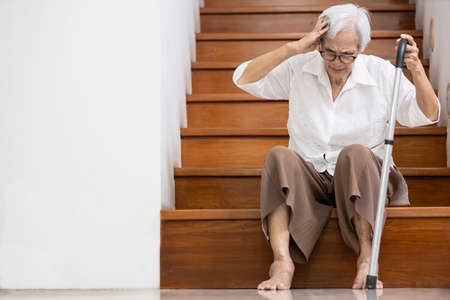 Asian senior woman have a severe headache,disease of brain tumor or brain cancer,pain in her head,sick old elderly sits on the floor of the stairs to rest her vertigo,dizzy,tendency to fall or stagger