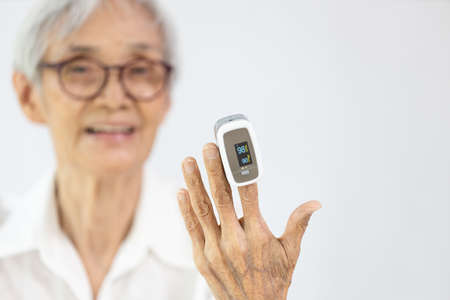 Hand of old elderly with fingertip pulse oximeter on finger for examination of oxygen saturation at home,measuring heart rate (pulse) Stock Photo