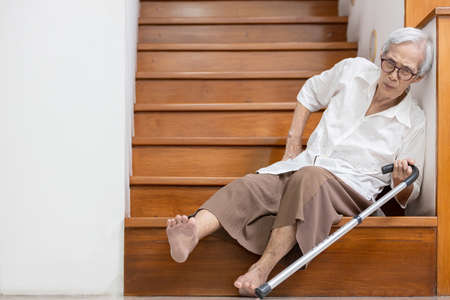 Senior woman sitting on the floor of the staircase with pain in hips and back,tripped or lose balance as she walked downstairs causing accidents,old elderly slipped and fell was injured by dizziness Banque d'images