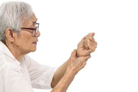 Old elderly was holding her painful wrist,inflammation of the wrist or flexor tendons,compression of carpal bones nerve,sensations of tingling,numbness in the her hands and fingers on white background Stock Photo