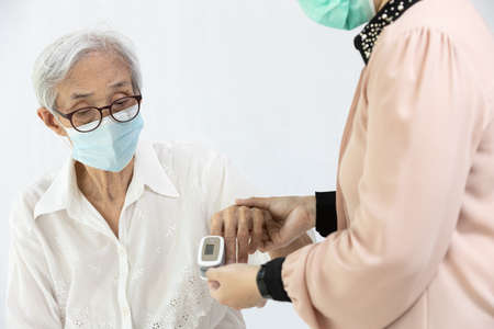Female caregiver with fingertip pulse oximeter,attached on finger of elderly,health check,measuring oxygen saturation level and rate of the heartbeat at home during COVID-19 or Coronavirus pandemic