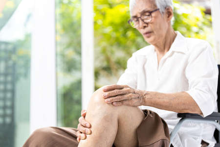 Close up,Leg of senior aged having pain in her knee,massage the kneecap with hands,joint disease,asian old elderly suffered severe Osteoarthritis,painful facial expressions,knee hurt when sitting down