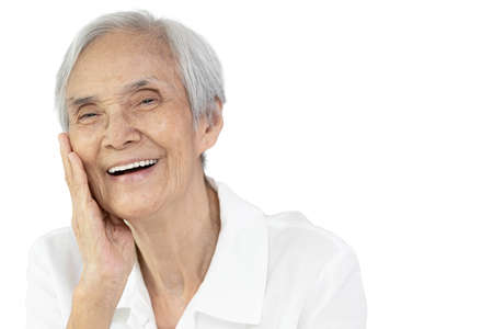 Asian senior woman with beauty face touch her cheek,enjoy healthy facial skin feels soft smooth,anti age,good personality,smiling old elderly show perfect strong clean white teeth,wide smile radiantly Stock Photo