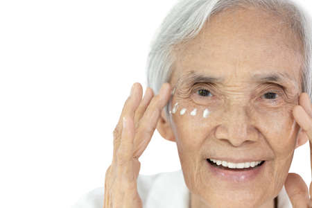 Close-up,Face of asian senior woman applying eye cream,anti-aging,nourishing under eye,facial treatment,happy smiling old elderly removing wrinkles crow's feet surrounding their eyes,skin care concept Stock Photo