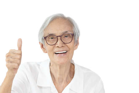 Happy asian old elderly wearing spectacles,raising hand sign,showing great thumbs up,smiling senior woman giving a thumbs up gesture,symbol of likes,good or success,isolated on white background