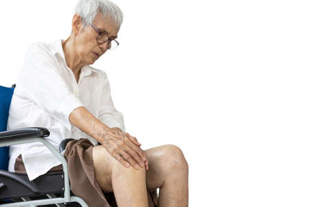 Leg of senior woman having pain in her knee joints,bone pain,hurt when bending the knee,holding knee cap with hands,facial expressions of pain,asian old elderly sitting in wheelchair,isolated on white