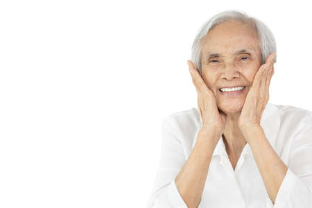 Smiling asian elderly woman with beautiful face skin touch her cheeks with hands, show perfect clean white teeth, feel of happy satisfaction, good health, healthy body and happiness in life, facial expression Stock Photo
