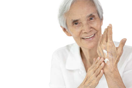 Asian senior woman applying baby lotion on hands, rubbing her palm with hands cream, moisturizer cream used to prevent dryness, nourish dry skin for the old elderly with sensitive skin,skincare concept