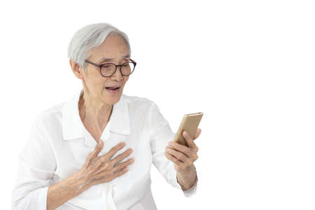 Relieved asian elderly who had waited anxiously for news via the hospital's online message for COVID-19 test results,feel at ease,safe from Coronavirus infection,good news about health on mobile phone