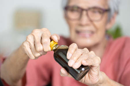 Asian senior woman hold a bottle of liquid drug,old elderly try to open the screw cap of bottle with difficulty,unscrew cap to open,hard to open,problem with weak hands or fingers,muscle weakness Stock Photo