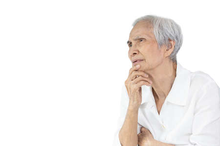 Concentrated senior woman touch her chin with hand,thinking,looking at copy space,thoughts,working of the brain,analytical thinking,solving puzzle in elderly,perplexity,contemplate,cerebration concept Stock Photo