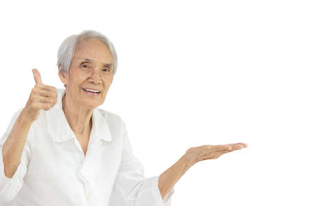 Senior people open the palm of hand on the empty copy space,elderly woman giving a thumb up gesture,symbol of likes,thumbs up for your excellent good quality product,presentation,advertisement concept