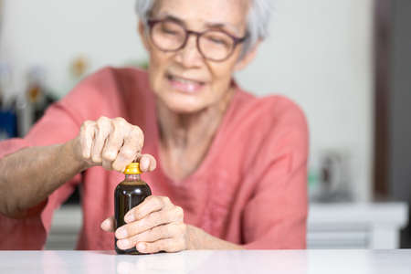 Trouble opening the lid of the bottle in the elderly aged,fingers without strength and weak,senior woman trying hard to open the screw cap,problem of hand weakness or wrist pain,numbness in the hands