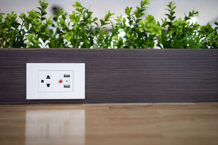 Electric power outlet socket with built in USB chargers on the table between seats for charging students' mobile phones or plugging in electrical appliances in restaurant or dining room at school Stock Photo