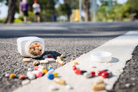 Plastic bottle of medication dropped on the street outdoor,drug scattered on the floor,jar of medicine with different pills tablets and capsules fall on the ground,should not be consumed,dirty unclean