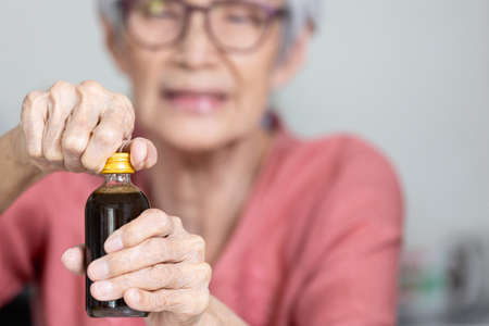 Asian senior woman trying hard to remove the screw cap,turn the bottle cap to open,trouble opening the lid of the bottle in the elderly aged or female people,difficulty in drinking,life problems Stock Photo