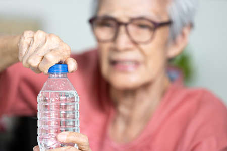 Trouble opening the bottle of drinking water in the elderly age,life problem,senior woman with numbness and weakness of hands and fingers muscle,difficulty in turning or unscrewing cap of water bottle