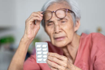 Asian old elderly trying to read medicine label that has small font,problem with very small letters of drug labels or tiny text on products information making her unable to see clearly what is written Stock Photo