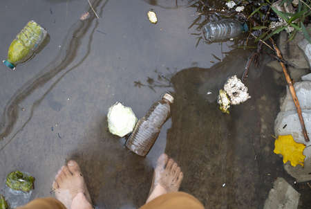 Legs of man standing barefoot or walking in flooded water on street,flooding road,risk of contagious disease and infection by contact with dirty water,cause of itchy skin,athlete's foot or tinea pedis