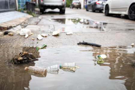 Garbage and dirty water,lot of rubbish scattered all over the street after heavy rains and flooding,dirt of debris,pieces of waste,plastic bottles floating in the flood,environmental pollution problem