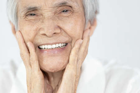 Happy senior woman is smiling confidently at beauty of new denture,false teeth in her mouth,beautiful old elderly showing new teeth after treatment,orthodontics,oral hygiene,dental health,care concept