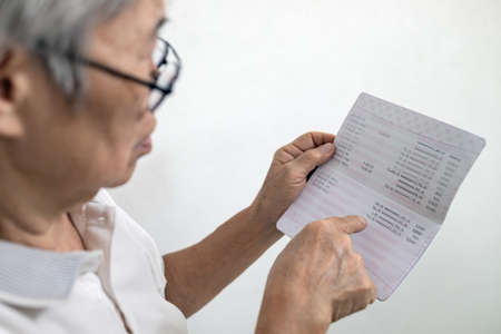 Hands of senior woman holding saving account passbook,checking the sum of money kept and check the amount of elderly pension and subsistence allowance deposits in a bank account,finance in retirement