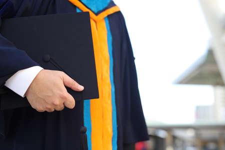 关闭骄傲的毕业生投入手和庆祝与证明在手中和感觉如此幸福在开始的天,学生祝贺在毕业日,教育成功概念