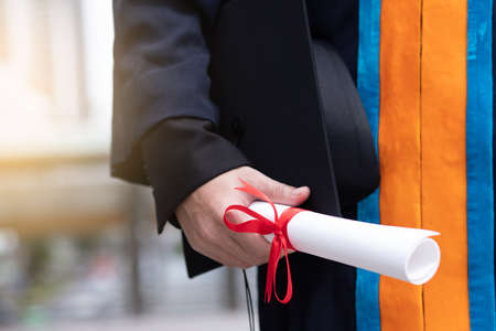 Happy graduate holding diploma education concept.