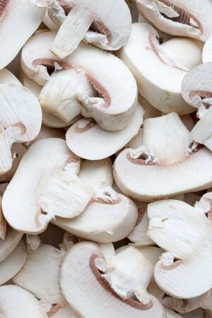 Fresh white champignons, sliced, uncooked, background, full