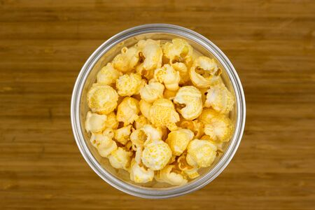 close up of popcorn in a plastic cup. fast food, junk-food and unhealthy eating concept.