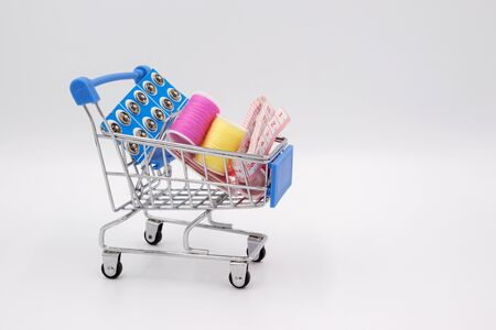 Sewing kit: thread, needles, measuring tape, buttons in a shopping cart on a white background. Concept of needlework, household, hobby, craft, buying items for creativity, household.