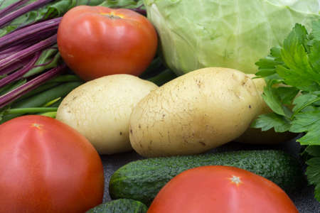 Fresh vegetables on a gray worktop, closeup: Potatoes, green onions, dill, tomato, parsley. Healthy food, vegan food.