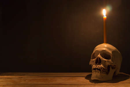Human skull with candle light on wooden table in the dark background, Decorate for Halloween Theme with copy space.