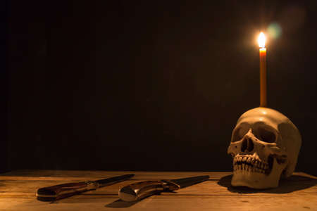 Human skull with candle light and knife on wooden table in the dark background, Decorate for Halloween Theme with copy space.