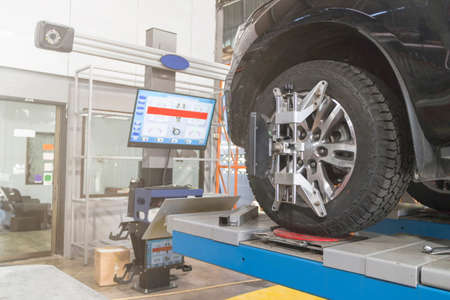 A Car on the Car Steering Wheel Balancer and Calibrate with laser reflector attach on each tire to center driving adjust in the garage 免版税图像