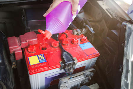 Mechanic hold a bottle of Distilled water for battery and fill for battery in the garage.