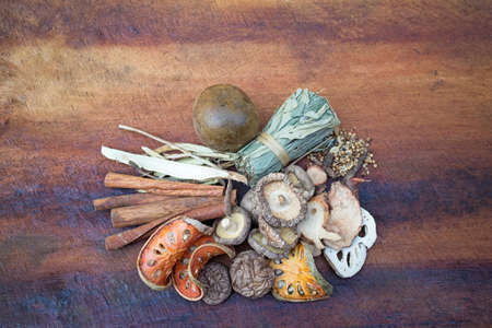 Top view of Dried mushrooms, Dried bael, Cinnamon and Dried herbs or spices on a wooden table, image with copy space for text or image.