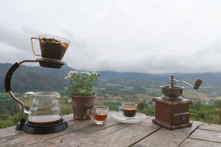 Morning cup of coffee with Rotary Coffee Grinder and Flower Pot on the wooden table with mountain background at sunrise and sea of mist, image with copy space.