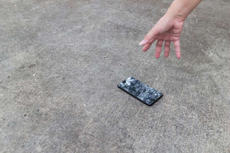 Smartphone fall out of hand and fall to the cement floor and the touch screen is broken. Foto de archivo