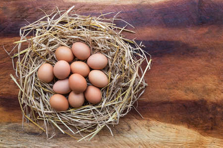 Top view of Chicken, Easter eggs in nest on a wooden table background, image with copy space.